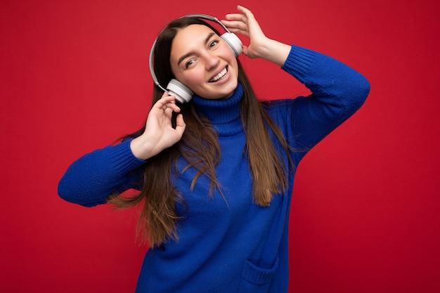 Aantrekkelijke positieve jonge donkerbruine vrouw die blauwe sweater draagt