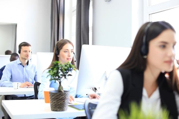 Aantrekkelijke positieve jonge ondernemers en collega's in een callcenterkantoor