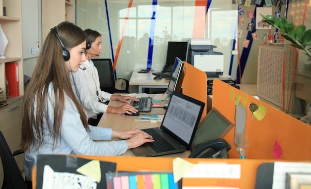 Aantrekkelijke positieve jonge ondernemers en collega's in een callcenterkantoor.
