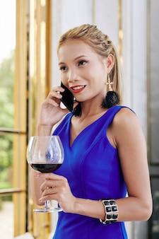 Aantrekkelijke positieve jonge verklede vrouw rode wijn drinken en praten over de telefoon met vriend
