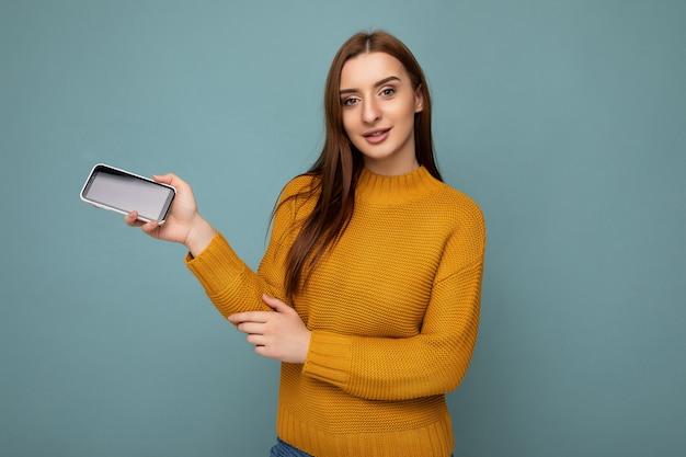 Aantrekkelijke positieve jonge vrouw, gekleed in oranje trui poising geïsoleerd op blauw