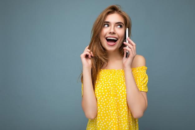 Aantrekkelijke positieve sexy glimlachende jonge blonde vrouw, gekleed in stijlvolle gele zomerjurk staande geïsoleerd