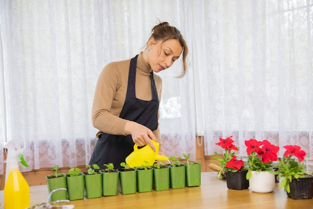 Aantrekkelijke positieve vrolijke vrouw bloemen met gieter water geven na het planten in zaailingen potten