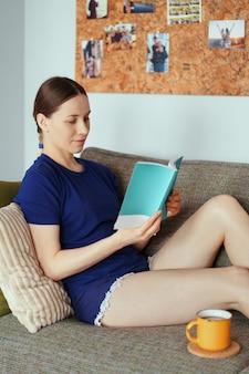 Aantrekkelijke positieve vrouw die een boek leest dat op de bank ontspant