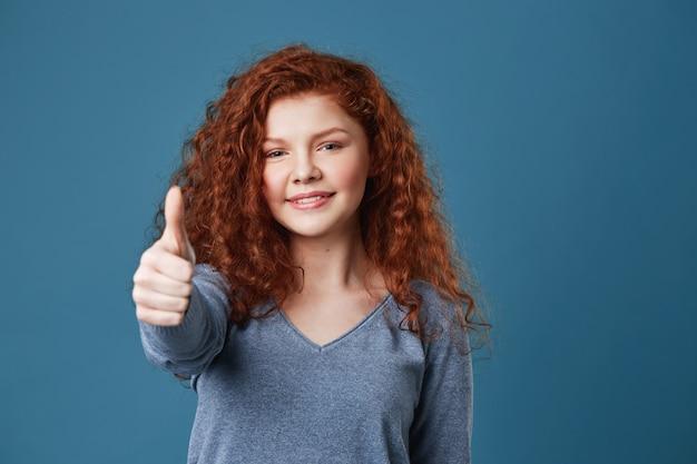Aantrekkelijke redhead vrouw met sproeten die duim met gelukkige en verrukkelijke uitdrukking tonen. kopieer ruimte.