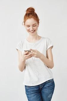 Aantrekkelijke redhead vrouw met sproeten glimlachen die telefoon bekijkt.