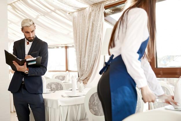 Aantrekkelijke restaurantmanager beoordeelt het werk van de serveerster