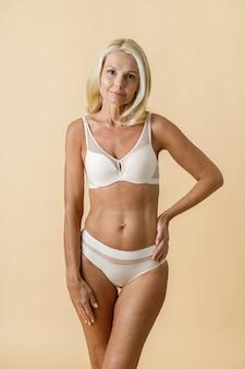 Aantrekkelijke rijpe blonde vrouw met perfecte lichaamsvorm in wit ondergoed kijken camera holding