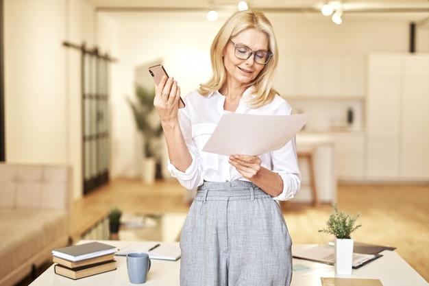 Aantrekkelijke rijpe blonde zakenvrouw met een oproep op de luidspreker om papieren te bespreken die binnen staan