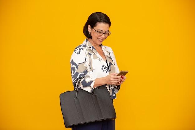 Aantrekkelijke rijpe onderneemster die met haar mobiele telefoon werkt