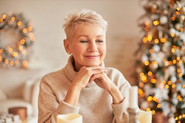 Aantrekkelijke rijpe vrouw in feestelijke stemming anticiperen op nieuwjaar denken over cadeaus voor familie, zittend in de woonkamer, omgeven met versierde kerstboom, krans en garland lichten