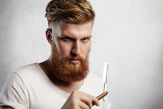 Aantrekkelijke roodharige hipster-kapper met stijlvol kapsel en dikke baard met een scheermesje, met ernstige gezichtsuitdrukking.