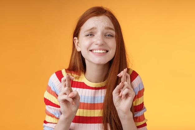 Aantrekkelijke roodharige hoopvol meisje anticiperend op goed nieuws opwinding sensatie kruis vingers veel geluk breed glimlachen bidden wens uitkomen goede resultaten ontvangen prijs, staande oranje achtergrond verlangen.