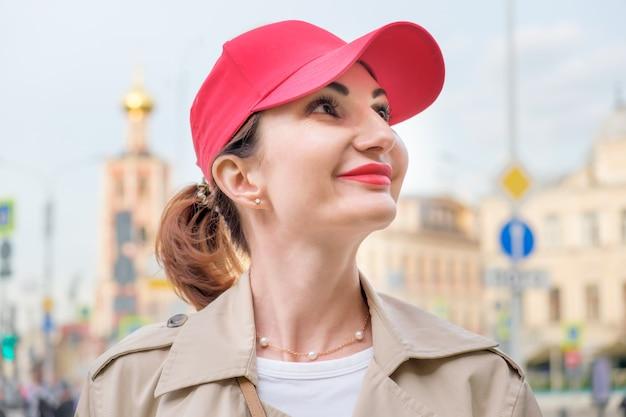 Aantrekkelijke roodharige jonge vrouw in een rode baseballpet en beige regenjas staat tegen de achtergrond van stadsgebouwen en kijkt op. portret van een lachende vrouw close-up. wandelen door de stad.