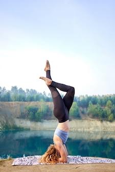 Aantrekkelijke roodharige krullende vrouw of model beoefenen van yoga buitenshuis