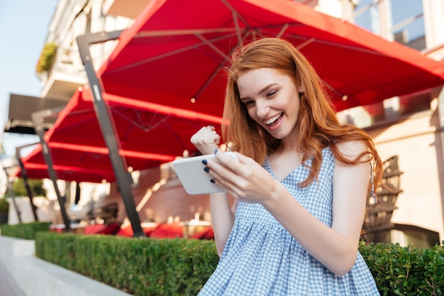 Aantrekkelijke roodharige meisje spelen van games op mobiele telefoon