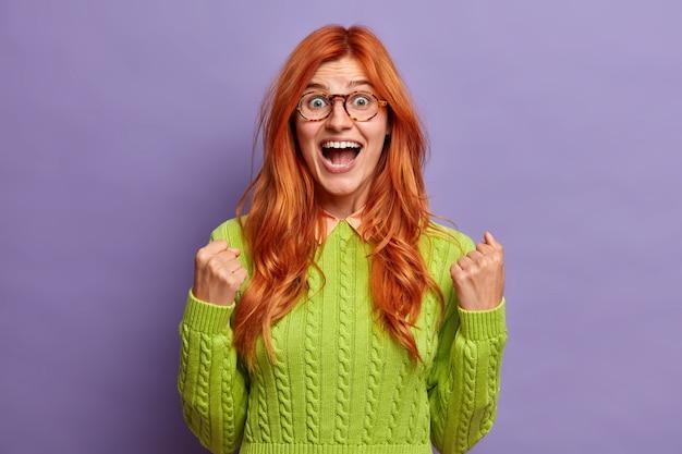 Aantrekkelijke roodharige vrouw balt haar vuisten met succes roept uit en voelt triomf, verbaasd, kan niet geloven dat haar overwinning een groene trui draagt.