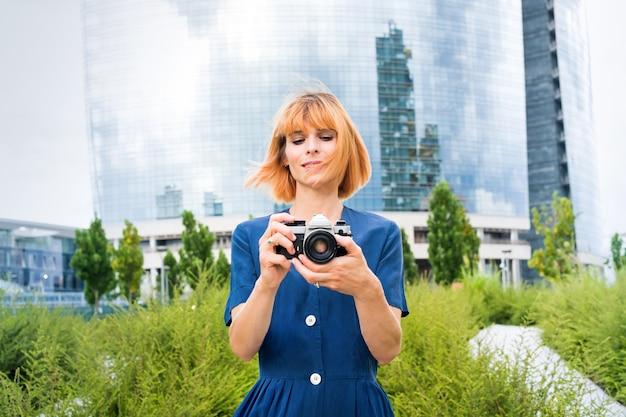 Aantrekkelijke roodharige vrouw die foto's maakt met haar camera in de stad tegen een achtergrond van groen en een modern glazen torenblok op een winderige zomerdag