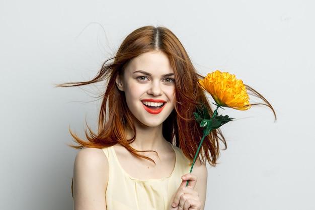 Aantrekkelijke roodharige vrouw met gele bloem in de buurt van de studio van de gezichtglamour