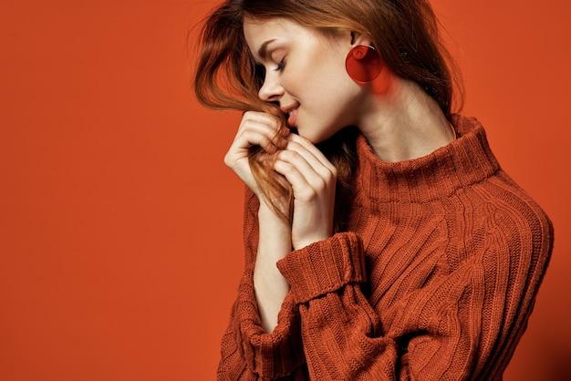 Aantrekkelijke roodharige vrouw rode trui oorbellen sieraden mode