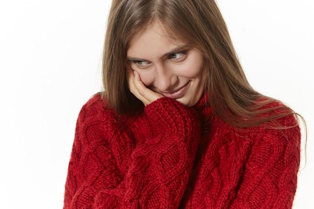 Aantrekkelijke schattige jonge vrouw met los glanzend haar neerkijkt met verlegen verlegen glimlach, beschaamd gevoel in ongemakkelijke situatie