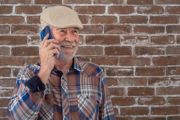 Aantrekkelijke senior man casual kleding staande tegen een bakstenen muur met behulp van telefoon en glimlachen.