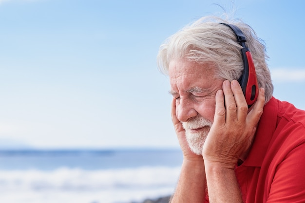 Aantrekkelijke senior man met witte baard en gesloten ogen zittend op het strand luisteren naar muziek met koptelefoon. blauwe lucht en horizon over zee