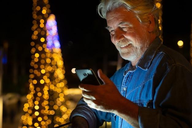 Aantrekkelijke senior man met witte baard en haar messaging met de mobiele telefoon. buiten in de nacht met een kerstboom achter hem. gele lichten decoraties.