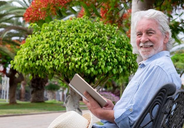 Aantrekkelijke senior man met witte baard glimlacht zittend in het park een boek te lezen