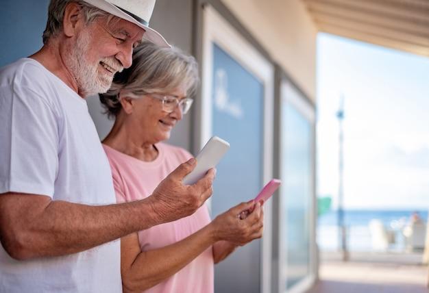 Aantrekkelijke senior paar modern en tech met behulp van slimme telefoon buiten op zee. in de schaduw staan met telefoon afgestemd op kleding