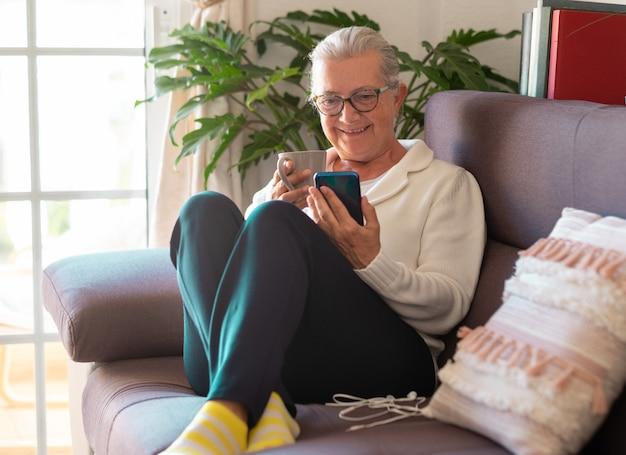 Aantrekkelijke senior vrouw grijsharig in quarantaine als gevolg van coronavirusinfectie zittend op hoest thuis met een kopje thee kijkend naar mobiele telefoon