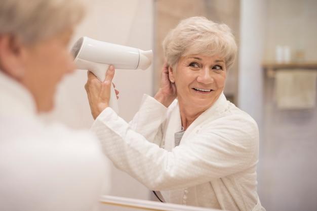 Aantrekkelijke senior vrouw in de badkamer