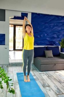 Aantrekkelijke senior vrouw thuis trainen, yoga of pilates oefening doen