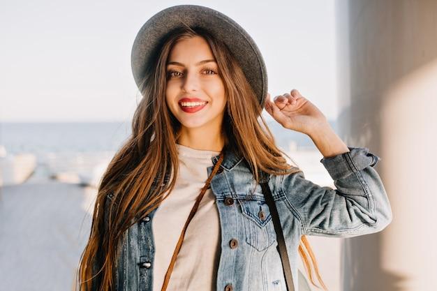 Aantrekkelijke sensuele jonge vrouw in trendy hoed glimlachend en poseren met hand omhoog op de achtergrond wazig.