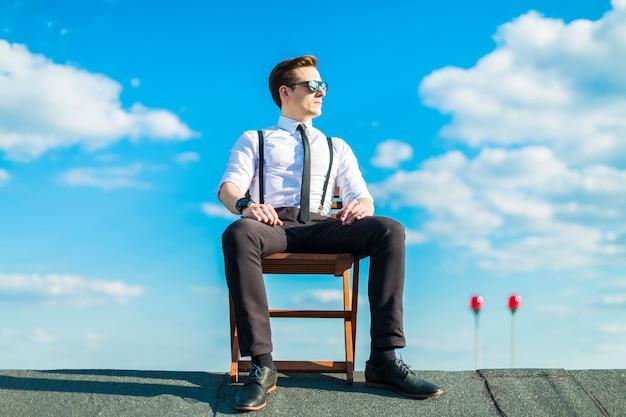 Aantrekkelijke serieuze busunessman in wit overhemd, stropdas, bretels en zonnebril die op het dak rusten