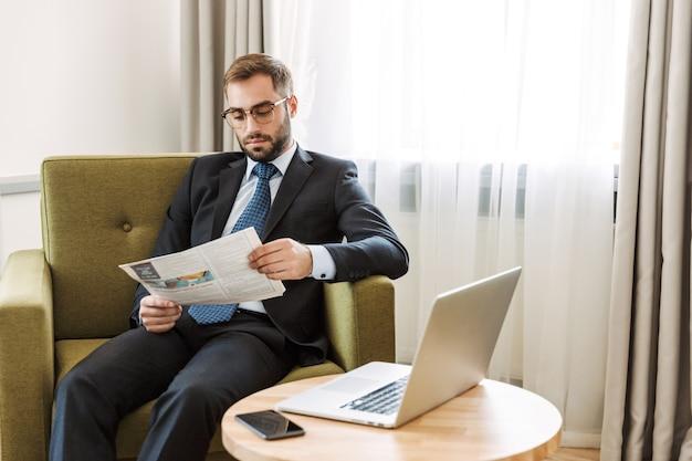 Aantrekkelijke serieuze jonge zakenman die een pak draagt, zittend in een stoel in de hotelkamer, de krant leest