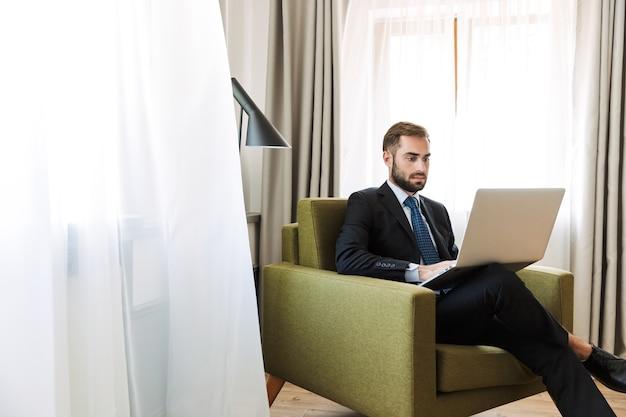 Aantrekkelijke serieuze jonge zakenman met een pak zittend in een stoel in de hotelkamer, werkend op een laptopcomputer