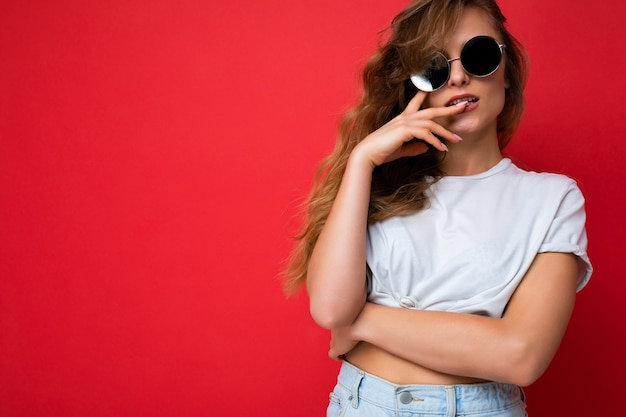 Aantrekkelijke sexy jonge blonde vrouw die alledaagse stijlvolle kleding en moderne zonnebril draagt