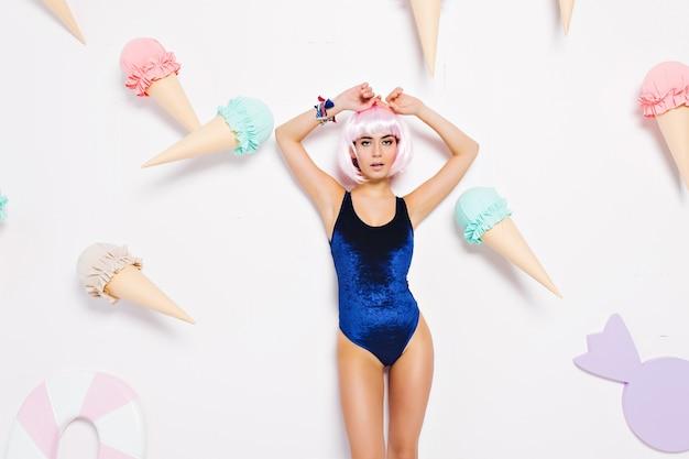 Aantrekkelijke, sexy, modieuze jonge vrouw die in zwempak onder groot roomijs ontspannen. pastelkleuren, snoep, genieten, ontspannen, vreugde, stijlvol, geïsoleerd.