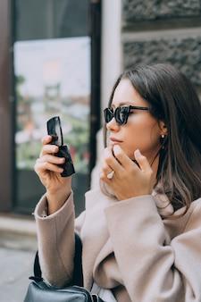 Aantrekkelijke sexy vrouw kijkt in een kleine spiegel en corrigeert make-up