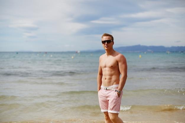 Aantrekkelijke shirtless atletische jonge man op het strand door zee. jonge gespierde man met een perfect lichaam in korte broek en zonnebril wandelen door de zeekust. reismode. sport levensstijl