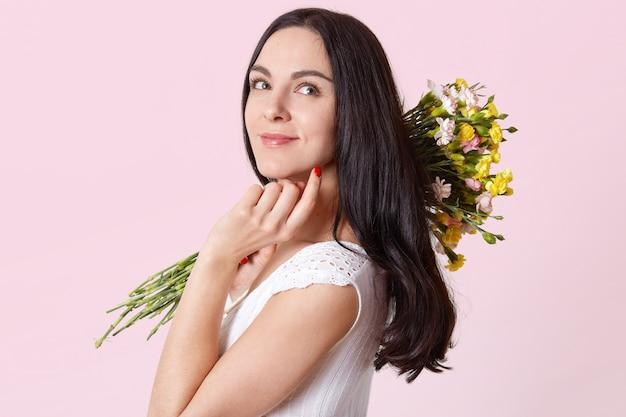 Aantrekkelijke slanke jonge dame houdt bloemen op haar schouder, raakt kin met vingers aan, zijwaarts staand, kijkend in een andere richting