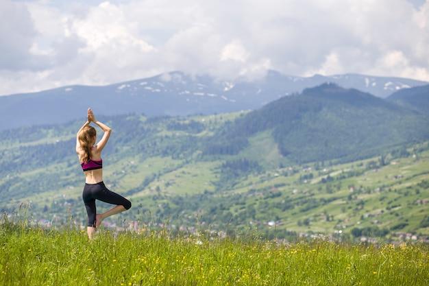 Aantrekkelijke slanke jonge vrouw die yogaoefeningen in openlucht op achtergrond van groene bergen op zonnige de zomerdag doet.
