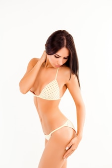 Aantrekkelijke slanke vrouw in lingerie aan haar heup te raken