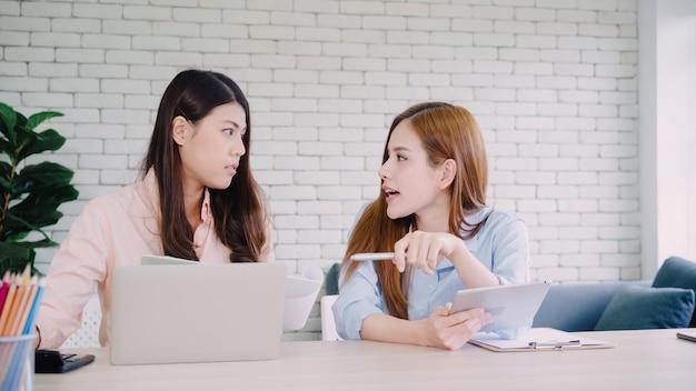 Aantrekkelijke slimme creatieve aziatische bedrijfsvrouwen in slimme vrijetijdskleding die aan laptop terwijl het zitten werken