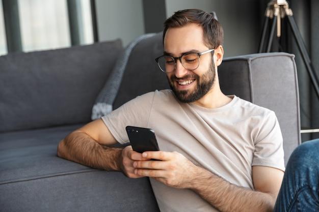 Aantrekkelijke slimme jonge man zittend op een vloer in de woonkamer, met behulp van mobiele telefoon