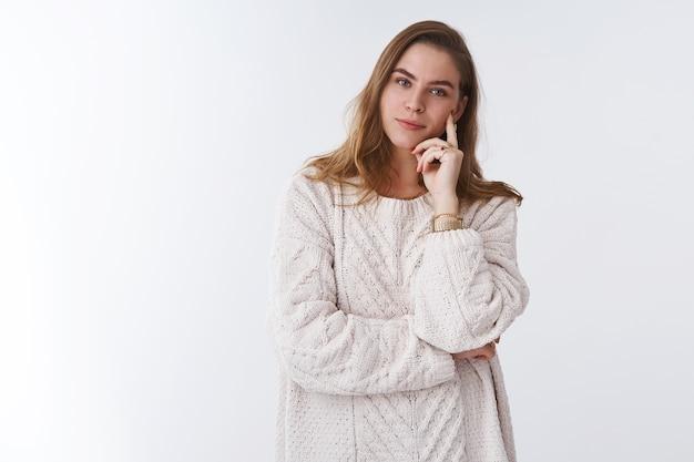 Aantrekkelijke slimme tedere jonge europese vrouw, gekleed in losse, gezellige warme trui, rustende open haard, kantelend hoofd aanraken van wang genietend van comfort glimlachend gelukkig, ontspannen zorgeloze witte achtergrond