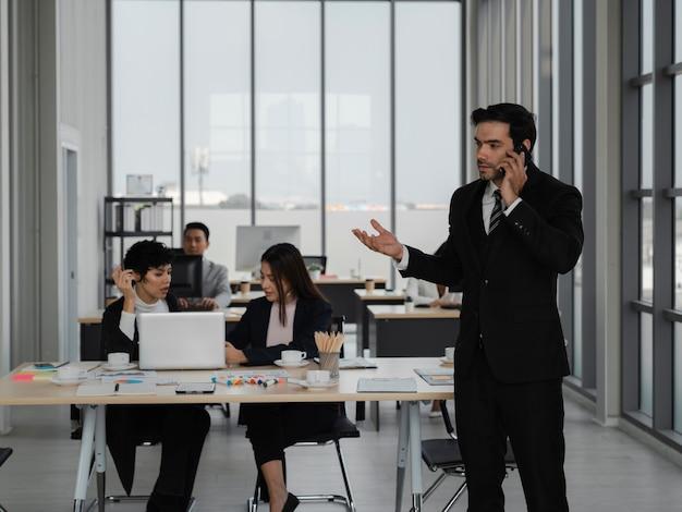 Aantrekkelijke slimme zakenman neemt mobiele telefoon op kantoor met diversiteitsmensen die erachter werken, zakelijk succes, ceo, analyse en strategieconcept