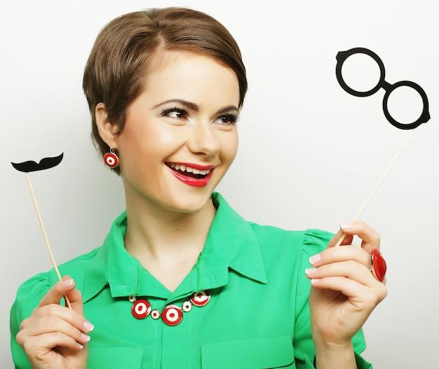 Aantrekkelijke speelse jonge vrouw met snor en bril op een stokje. klaar om te feesten.