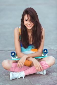 Aantrekkelijke sportieve aziatische vrouw in swimsuite glimlachend en zittend met skateboard op stoep binnen